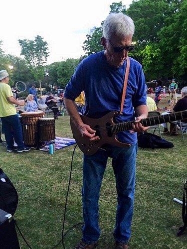 man playing electric guitar at drum circle