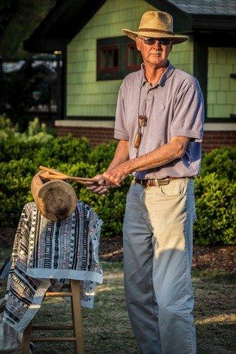 man playing a log drum called a krin