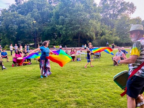 woman dancing with fan flags in drum circle