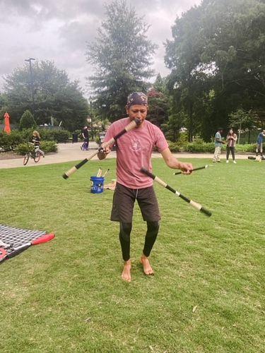 man juggling sticks